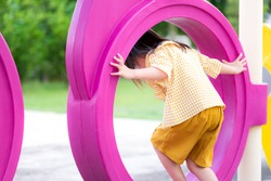 A girl in yellow dress is playing, climbing in a playground equipment. Photos on the back. Safety care concept and leisure activities. Asian children aged 4 years.