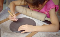 A girl inspecting a slab of clay, piercing air bubbles off her clay to prevent cracking when baked.