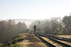 A girl is balancing on narrow gauge train tracks over bridge with sign no trespassing in Ankysciai, Lithuania