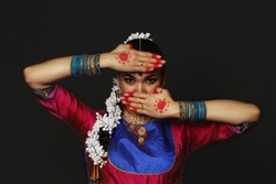 A girl is dancing an Indian dance. A dancer dances in a studio on a black background.