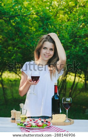 a girl is drinking wine at the dinner table in the garden