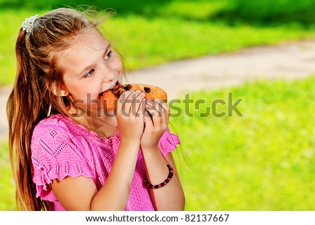 A girl is eating her hot dog outdoors. - stock photo