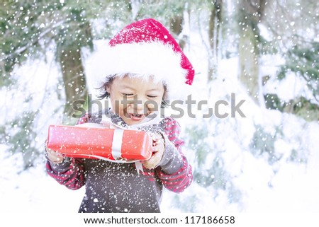 A girl is excited to open her Christmas present during winter season