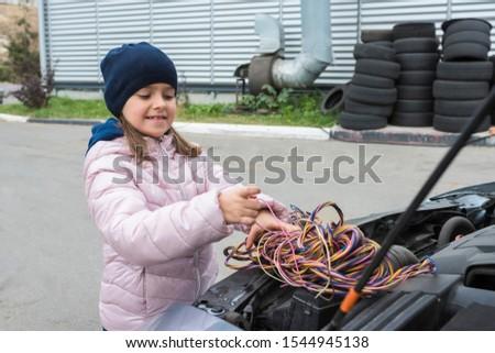 A girl is fixing a car. Repair service. Car service.