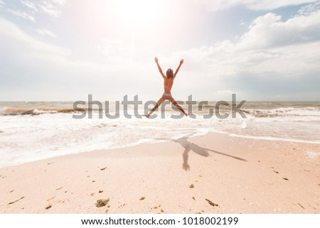 A girl is jumping on the beach and placing her hands wide. A slender woman is resting on the sea coast. Brunette on the shore of the ocean. Fitness in nature. #1018002199