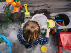 a girl is playing at her mud kitchen in the garden
