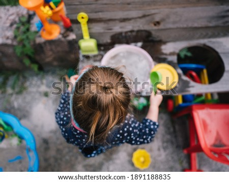 a girl is playing at her mud kitchen in the garden Stock photo ©