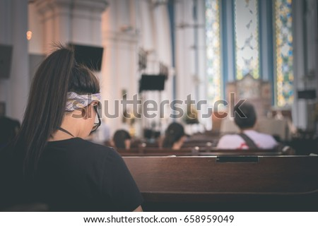 A girl is praying in the church. #658959049