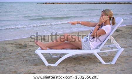 A girl is relaxing on a deck chair by the sea among the waves rolling on the shore. Holding the phone in his hands. Notices something unusual and screams ecstatically