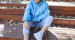 A girl is sitting on a park bench in a blue oversized hoodie.fashion and wear concept. warm oversize wear at female.space for text and logo.close up details of oversize wear.mock up.sneakers at model