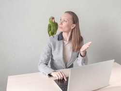 A girl is sitting with a green parrot on her shoulder at the computer discussing a business idea.