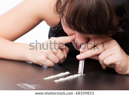 a girl is sniffing cocaine (imitation). isolated on a white background