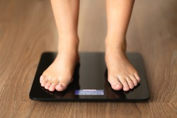 A girl is standing on the scales on a wooden floor. Close legs plan on the scales. Track changes in your weight. Losing weight.