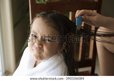 a girl is upset face, she got head lice from a school friend and do combing treatment