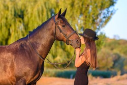 A girl kisses a horse in the rays of the setting sun