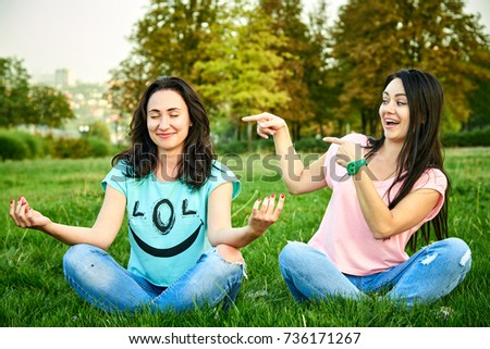 A girl laughs at a friend who meditates in the park #736171267