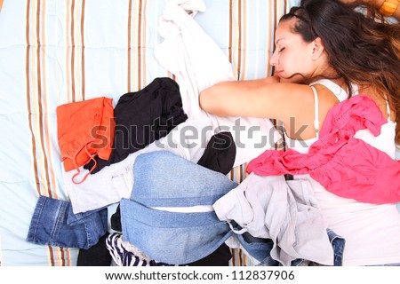 A girl laying in between of a bunch of clothes.