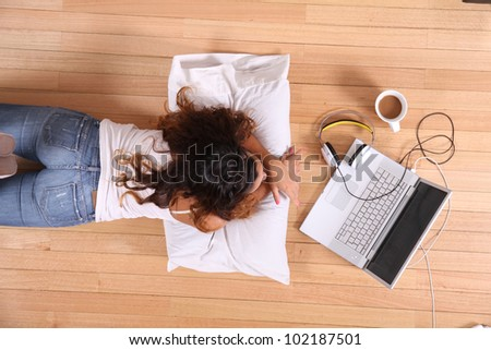 A girl laying on the Floor while surfing on the Internet with a Laptop.