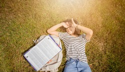A girl lying on the meadow with a book and a bag on the side