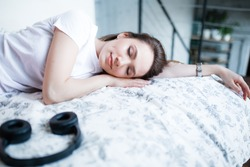 A girl of European appearance sleeps on the bed next to the headphones. Fell asleep after listening to music and meditation.