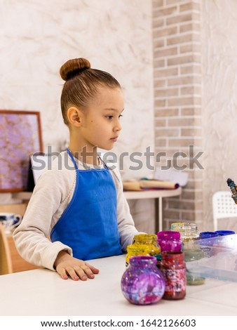"""A girl of 6 years old examines paints, brushes and devices for working in the Ebru technique. Ebru Art, the Ancient Techniques of """"Painting on Water"""""""