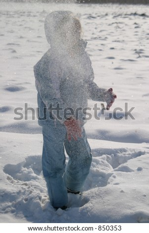 A girl on the snow throwing a snow ball