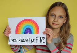 A girl on yellow background holds a sheet of paper. She drew a rainbow and wrote phrase Everything will be fine. The concept of the hope that the pandemic of coronavirus Covid-19 will finish soon