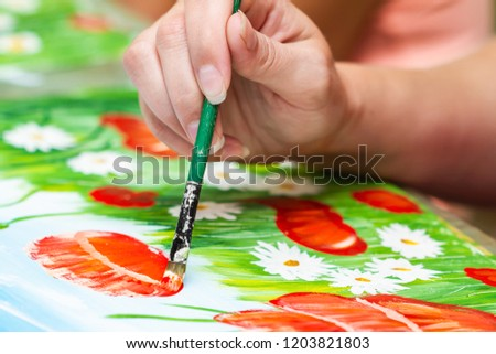 A girl paints a picture by gouache. A girl drawing poppies and chamomiles. The hand and paint brush. Closeup, selective focus