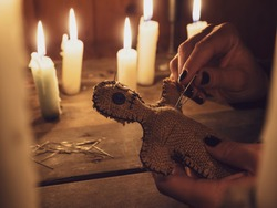 A girl pierces a voodoo doll with needles, close-up. Esoteric and occult rituals on a wooden table in a dark room with many candles. The concept of revenge, causing harm to a rival. Magic background.