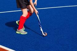 A girl playing field hockey on blue
