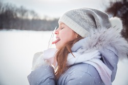 A girl playing with snow in winter, making snow angel and eating icicles