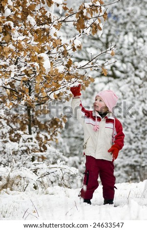 A girl playing with snow on a tree - stock photo