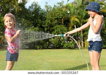 A girl pours water from a hose at my sister
