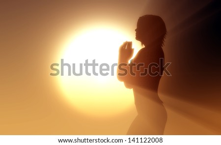 A girl prays in the rays of the sun.
