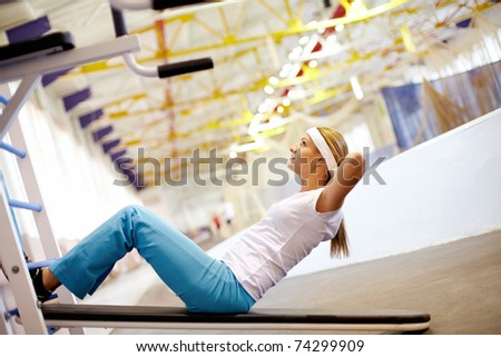 A girl pumping abdominal muscles in gym