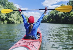 A girl rafts down the river on a kayak.