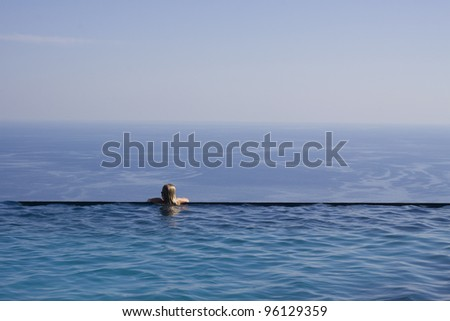 A girl resting at the end of a stunning infinity pool. Space for text