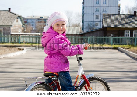 A girl riding a bicycle in the yard.