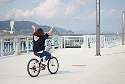 A girl riding a bike with no hands in Yeosu, Korea