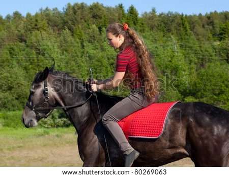 A girl riding a horse on a meadow