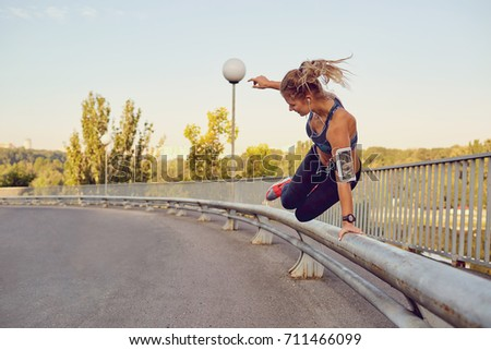 A girl runner jumps over a railing on a bridge in the city. #711466099