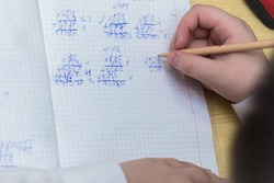 A girl's hand with a ballpoint pen close-up writes in bad handwriting. The student completes the task. A student solves examples in mathematics at school at a desk. Warm soft daylight.