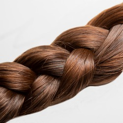 A girl's pigtail of dark brown hair. On a white background. Women's hair is braided in a braid. At close range. Hair style. Hair care.