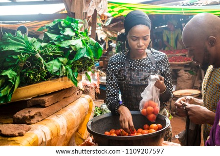a girl selling tomatoes to a guy in a local african market