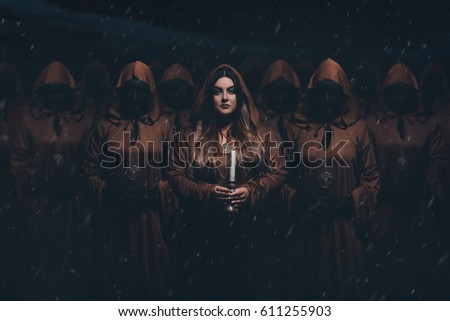 Stock Photo A girl servant wanders around with candles. A crowd of people in masks wearing robes. Creative colors