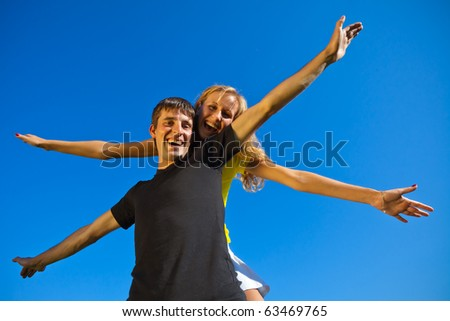 A girl sits astride the boy, and both arms wide apart, portray the aircraft in flight