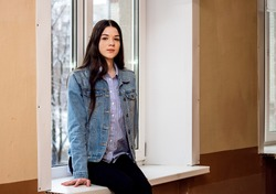 A girl sits on a white window