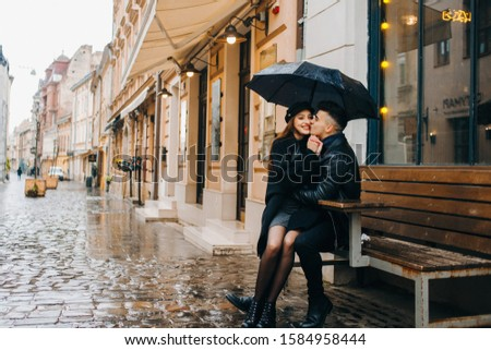 A girl sits on her lap in boyfriend that sitting on a bench near a cafe. Loving couple under umbrella on city street