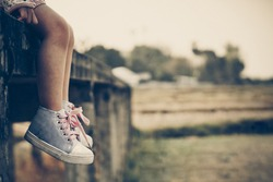 a girl sitting alone on a bridge with her feet pointing down in vintage tone