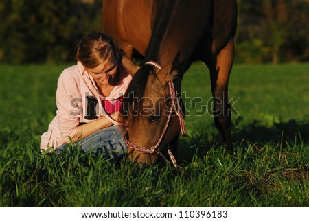 a girl sitting in the pasture beside her grazing horse